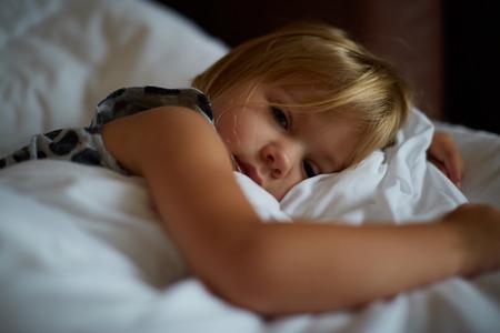 Linda niña rubia caucásica despertar en la cama por la mañana. El niño se despierta temprano para ir a la escuela. Estirarse y bostezar. Sueño saludable. Salud infantil. Foto de archivo