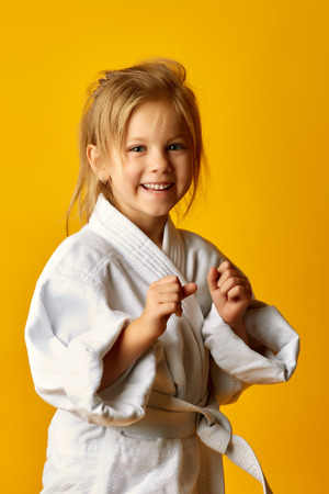 The karate girl on a yellow background with white belt is hitting right hand
