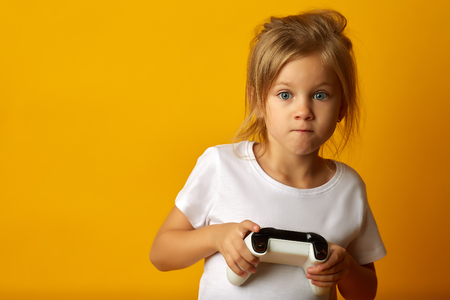 Little absorbed girl in white t-shirt holding game pad playing video game on yellow background