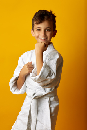 Happy little boy in white kimono of fighter standing in stance smiling at camera on yellow background