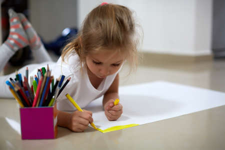 Adorable little girl lying on floor and drawing on huge paper sheet with yellow marker pen Фото со стока