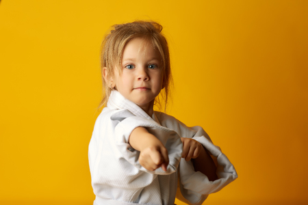 Charming little girl wearing white kimono and standing in fighting stance looking at camera on orange background