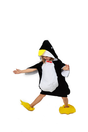 A little girl in penguin clothes is dancing on a wrinkle on a white background