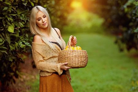 Sensual blond woman holding wicker basket full of seasonal fruit standing in green orchard
