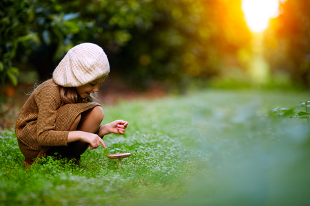 Side view of charming little girl in beret sitting on green lawn with growing mushroom smiling away