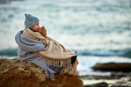 little girl with a teddy bear is sitting on a stone near the sea in a cold season, being wrapped in a warm blanket