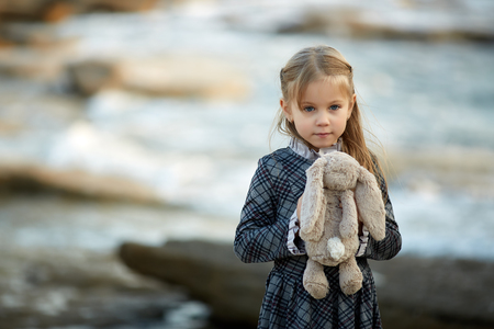 Little dreaming girl wearing an elegant dress while embracing small soft bunny toy standing on the coast