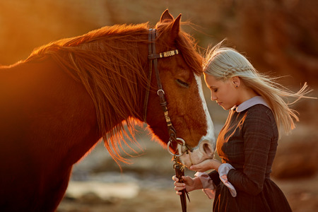 wind lifts the hair of a blonde woman in an elegant long dress walks with a horse along a beautiful rocky beach in the sunlight Reklamní fotografie