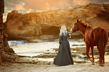 Blond woman wearing elegant long dress walking with horse on beautiful rocky seashore in sunlight