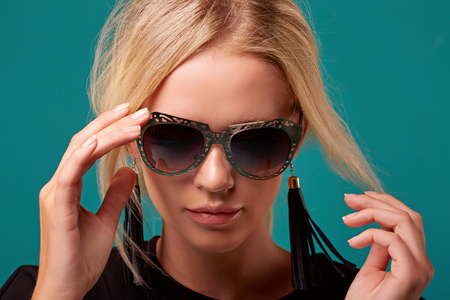 Close Up Fashionable Blonde in Retro Style Sunglasses on Turquoise Background