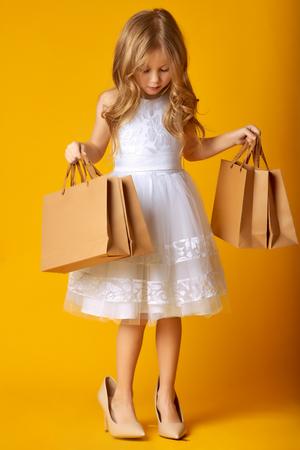 Verbaasd aantrekkelijk kind in jurk en grote schoenen met boodschappentassen op gele achtergrond. KINDERMODE Stockfoto
