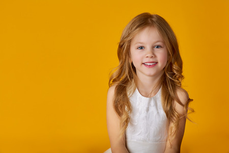 Kids fashion. Portrait of a cute 6 year old girl in a white dress posing on a bright yellow background. summer, summer fashion. Happy baby girl.