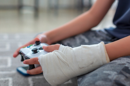 Child with broken arm using video game controller