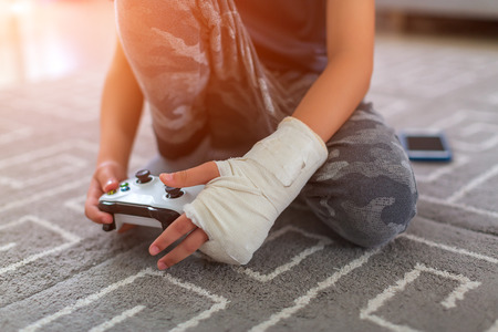 boy with injury at home. yonge video gamers hands using a gamepad Imagens
