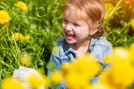 Kleines blondes Baby zwischen gelben Blumen, das lächelt und wegschaut