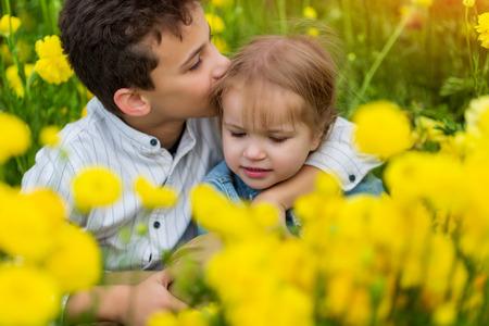 älterer Bruder umarmt und küsst seine jüngere Schwester auf dem Feld in gelben Blumen Standard-Bild