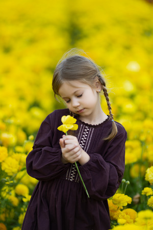 dreamy little girl in a burgundy dress with eyes closed, holding a yellow flower