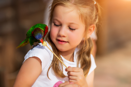 Cute little girl playing with a parrot and feed him
