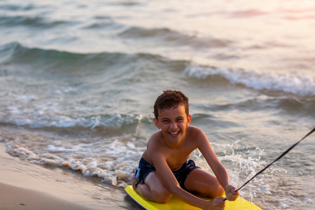 Happy baby boy young surfer ride on surfboard with fun on sea coast Reklamní fotografie
