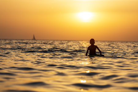 Silhouette of a boy floating on the sea with surfboard on the excellent background of orange sunset Reklamní fotografie