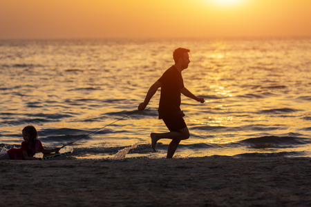 Father and kid playing on the beach at the sunset time. Concept of friendly family Reklamní fotografie