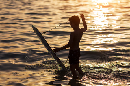 teenager with a surfboard on the background of the ocean waves
