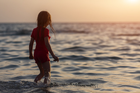 lonely little girl on the sea beach at the morning sunrise