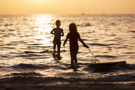 Happy children playing on the beach at the sunset time. Concept of summer vacation and friendly family