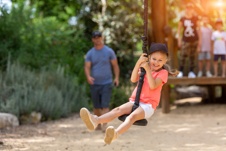 smiling girl riding a bungee in a park on the playground