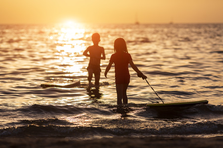 silhouettes of children during the summer holidays. relaxing at sea at the golden hour