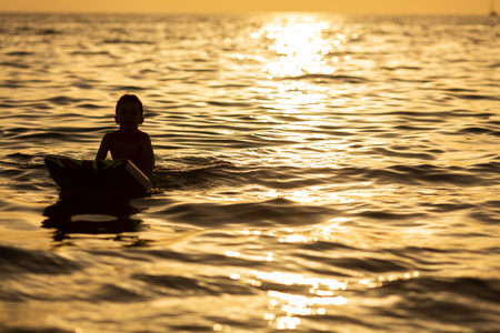alone boy silhouette on a board in the sea at sunset