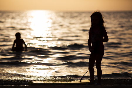 silhouette of a girl with a board on the background of the golden sea