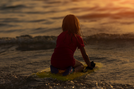 Happy Surfing girl on a beach looking on the sea and ready to go into the water. Sunset time Reklamní fotografie