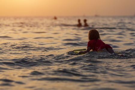 Surfer girl in bright swimsuit waiting for the wave in open water. Sunset time at the ocean Reklamní fotografie
