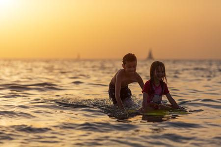 older brother rolls his sister over the sand on the body board Reklamní fotografie