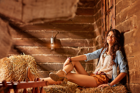 Young cowgirl sits on a bale of hay and smiles at the camera