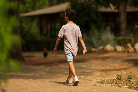 Little kid boy walking alone in the forest.