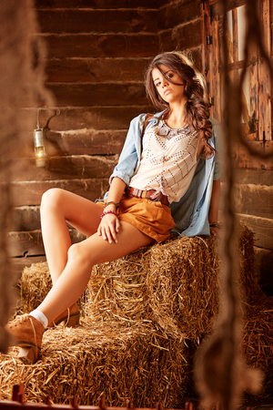 Romantic young hippy posing in a barn sitting on a hay