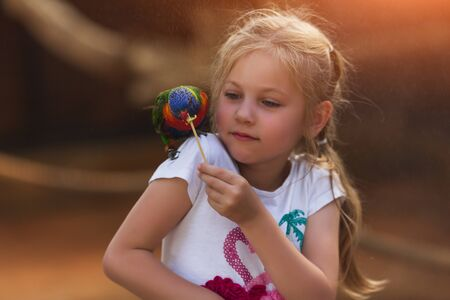 Charming little girl feeding multicolored parrot on shoulder