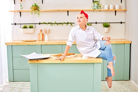 young blonde with a red headband in a white shirt sits on the kitchen table with dough for baking