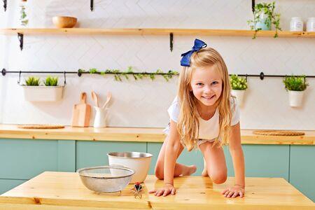 klein blij kind, schattig peutermeisje dat moeder helpt om heerlijke muffins in de keuken te bereiden