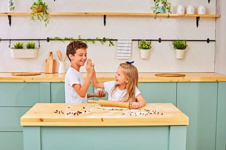 Happy loving family are preparing bakery together. brother and sister are cooking cookies and having fun in the kitchen. Homemade food and little helper. Stock Photo