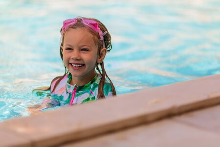Child with goggles in swimming pool. Little girl learning to swim and dive in outdoor pool of tropical resort. Swimming with kids. Healthy sport activity for children. Sun protection. Water fun.