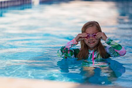 Portrait of cute happy little girl having fun in swimming pool. Kids sport on family summer vacation. Active healthy holiday