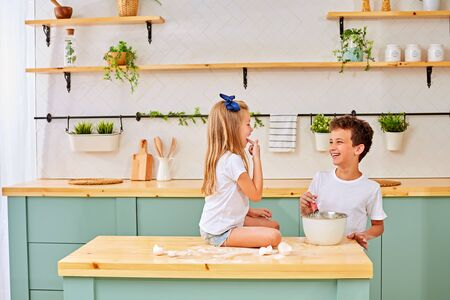 Cute kids, adorable little girl and boy making dough for a cake. Children mix flour, eggs and milk baking apple pie in sunny white kitchen with modern appliances 写真素材