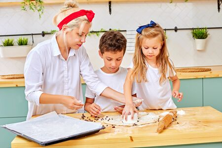 mother and his children are preparing flavored cookies in a spacious white kitchen. mom teaches his children to cook. Joint pastime with family 写真素材