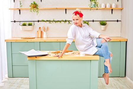 Trendy barefoot female looking at camera and smiling while sitting on kitchen table during pastry preparation at home