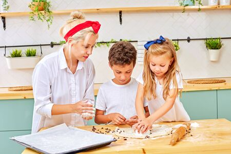 mother and his children are preparing flavored cookies in a spacious white kitchen. mom teaches his children to cook. Joint pastime with family.