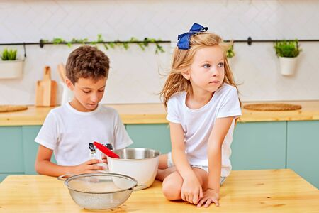 Little boy and girl mixing fresh dough for pastry in bowl while cooking in kitchen at home together
