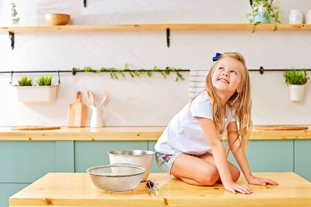 Happy little girl with blond hair cheerfully smiling and looking up while sitting on knees on wooden table near utensils in kitchen 写真素材